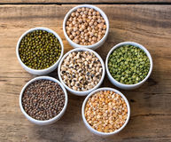 Six bowls with cereals on wooden desk. Six bowls with cereals (bean  pea lentil, haricot, kidney) on wooden desk set in a circular Royalty Free Stock Images