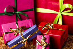 Six Bows Tied around Unicolored Gift Boxes. Four small and two larger presents with bow knots. Vibrant, plain colors. Background for many gift-giving occasions Stock Images