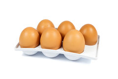 Six Brown Eggs in a White Plastic Package Isolated on White Stock Image