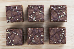 Six Brownies. Six chocolate brownies sprinkeled with silver stars from directly above Royalty Free Stock Photography