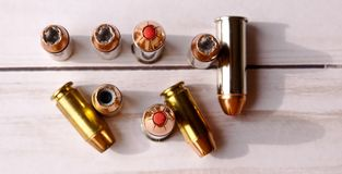 Six 40 caliber hollow point bullets along with three 44 special red tipped bullets shot from above. On a white wooden background royalty free stock images
