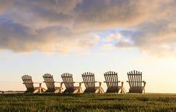 Six chaises d'Adirondack faisant face à la lumière du soleil intense de râtelage photos libres de droits