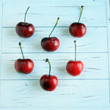 Six cherries on a white rustic wooden background Stock Images