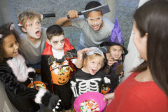 Six children in costumes trick or treat at house stock photo