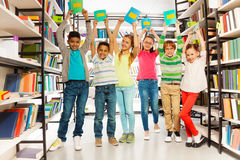 Six children with hands up hold exercise books Stock Photos