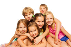 Six children sit hugging together Stock Photos