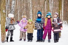 Six children  stand holding hands in winter park Stock Photos