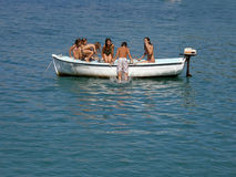 Six children in summer fun. Children (best friends) on school vacation, enjoy, swimming, sunbathing, on a small white board. Horizontal color photo Royalty Free Stock Photos
