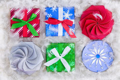 Six Christmas gift packages surrounded by feathers Royalty Free Stock Images