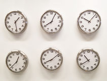 Six clocks on white wall. Six round clocks showing each one different time indication , against a white wall background Royalty Free Stock Photo