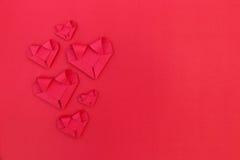 six coeurs de papier rouges fois sur le rouge pour le modèle et le Ba de valentine Images libres de droits
