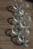 Six cognac glasses in two rows on the brown wood. With shadows Royalty Free Stock Photos