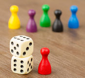 Six colored pawns and two dice Stock Image