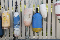 Six colorful boat buoys hanging on a white picket fence Stock Images