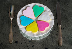 Six colorful multicolored hearts on the white plate Stock Photos