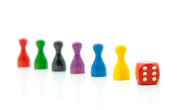 Six colorful pawns with red dice Stock Photography