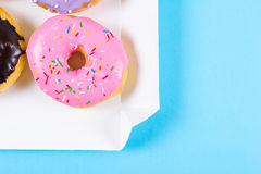 Six colorful round donuts in the box. Flat lay, top view. Royalty Free Stock Photo