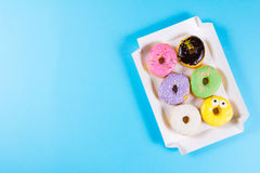 Six colorful round donuts in the box. Flat lay, top view. Stock Photography