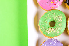 Six colorful round donuts in the box. Flat lay, top view. Royalty Free Stock Images