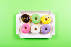 Six colorful round donuts in the box. Flat lay, top view. Stock Images