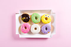 Six colorful round donuts in the box. Flat lay, top view. Royalty Free Stock Photos