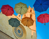Six colorful umbrellas against gothic cathedral and blue sky. Stock Photos