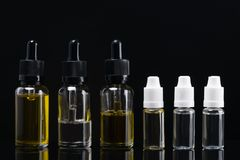Six containers with aromatic liquids on a black background with reflections Stock Photo