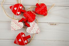 Six cute decorated hearts as clothespins laying on white wooden table. Top view, space for text stock photo