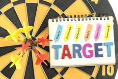 Six dart in bullseye with words target on the notebook with hand. Writing timely achievable relevant goals education teamwork over dartboard background, Business Stock Photography