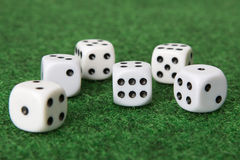 Six dice. On green mat with focus on six dots on one dice Royalty Free Stock Photography