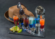 Six different colored shot drinks, lined up on a black stone pla. Te, ice cubes in shaker and ice tongs, lemon and lime, brown hat, brown sunglasses, party set Royalty Free Stock Photos