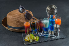 Six different colored shot drinks, lined up on a black stone pla. Te, ice cubes in shaker and ice tongs, lemon and lime, brown hat, brown sunglasses, party set Royalty Free Stock Photo