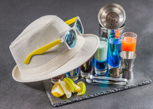 Six different colored shot drinks, lined up on a black stone pla. Te, ice cubes in shaker and ice tongs, lemon and lime, white hat, yellow sunglasses, party set Stock Image