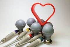 Six ECG electrodes with heart shaped cutter. Six ECG electrodes with heart shaped gingerbread cutter and patient cable connected stock photos
