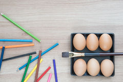 Six Eggs in black square plate with a brush and color pencils Royalty Free Stock Photo