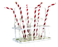 Six empty bottles of milk with drinking straws in crate on white Royalty Free Stock Images