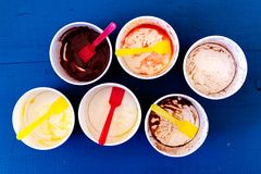 Six empty messy ice cream paper cups with yellow and red plastic Royalty Free Stock Image