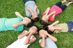 Six enfants jouant en parc Image libre de droits