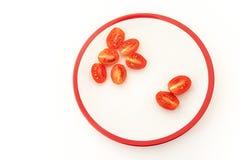 Six et deux moitiés des tomates-cerises rouges du plat blanc Photographie stock