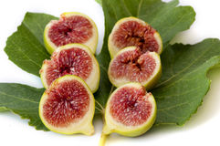 Six fig halves, red and juicy, on a green leaf. Three green figs cut open to show the juicy and sweet red seeds. on a green fig leaf, on white Stock Images