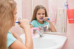 Six filles d'ans nettoient des dents à vision latérale dans le miroir dans la salle de bains Image libre de droits