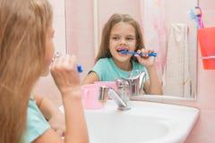 Six filles d'ans nettoient les dents avant inférieures regardent dans le miroir dans la salle de bains Photographie stock