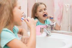Six filles d'ans nettoient les dents latérales inférieures regardent dans le miroir dans la salle de bains Photo stock