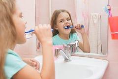 Six filles d'ans nettoient les dents latérales supérieures regardent dans le miroir dans la salle de bains Photo libre de droits