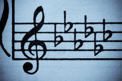 Six flats: E flat minor or G flat major. Old-looking blue washed grungy music manuscript with treble clef and key signiture of six flats Royalty Free Stock Photo