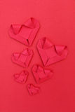 Six folding red paper hearts on red for valentine pattern and ba. It is six folding red paper hearts on red for valentine pattern and background Royalty Free Stock Photo