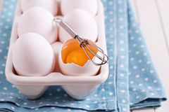 Six fresh eggs in egg holder with one cracked egg Royalty Free Stock Image