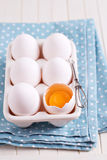Six fresh eggs in egg holder with one cracked egg Stock Photo