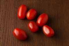 Six fresh red cherry tomatoes on a wood table Stock Images