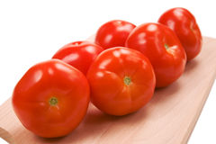 Six fresh red tomatoes on cutting board Royalty Free Stock Photos
